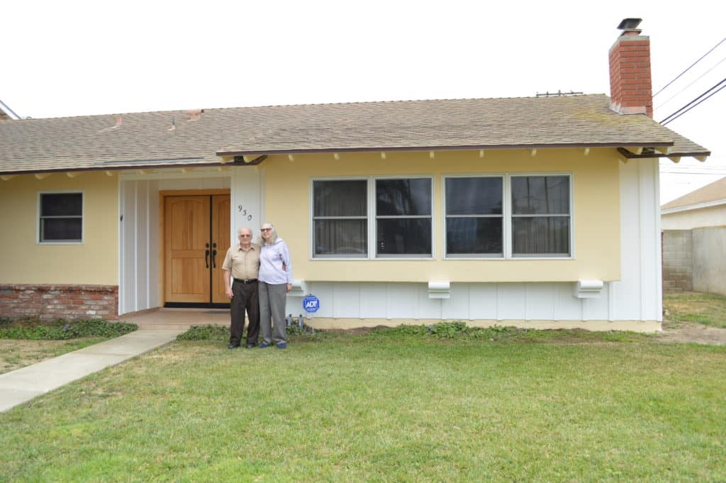 elderly couple stand in front of home with chimney