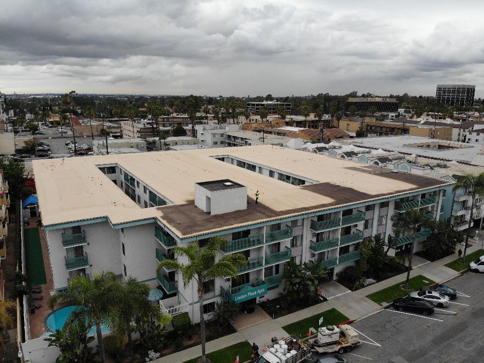 commercial roofing services for apartments - An aerial view of the Linden Plaza Apartments roof, with workers applying the final coating to the apartment roof.