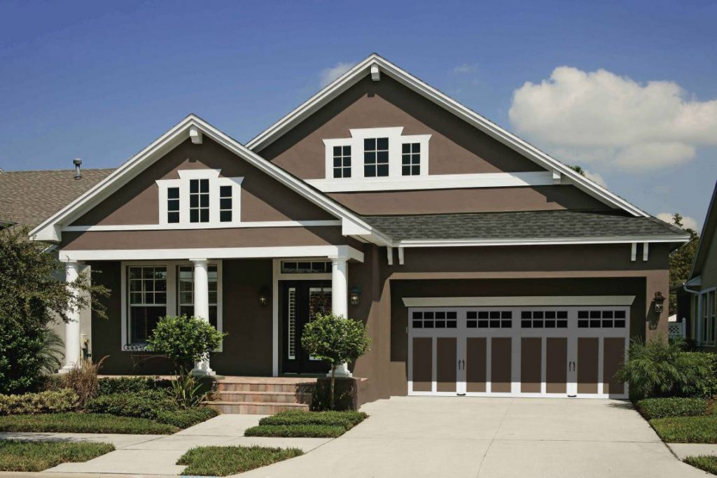 Exterior Painting - A brown home with white trim and a coordinating garage door.