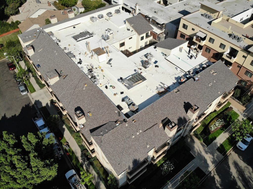 Newly replaced roof for a commercial building with multiple roofing types.