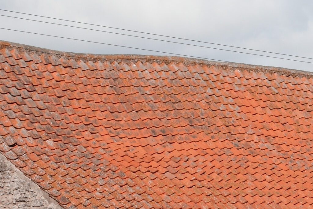 A Spanish tile roof with sagging shingles.