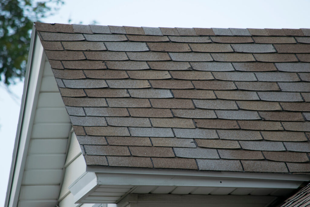 Roof of a residential house showing damage, multiple layers of shingles, missing shingles.